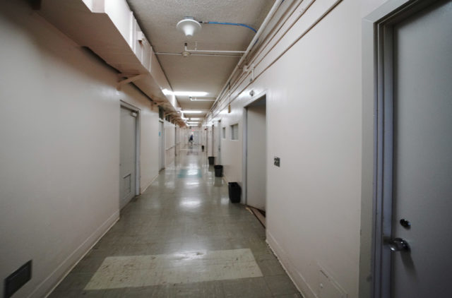 Staff enters a locked door down a long hall in the State Hospital/Guensberg Building.