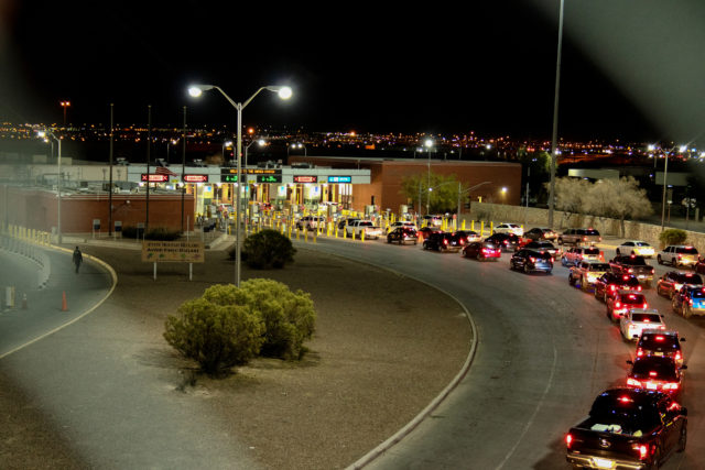 Night time crossing at the international border between the United States and Mexico with long lines of vehicle traffic waiting to get through to the other side.