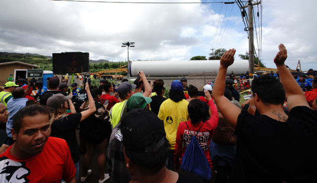 Kahuku wind turbines arrive off of Kamehameha Highway as protestors shout 'hewa'.