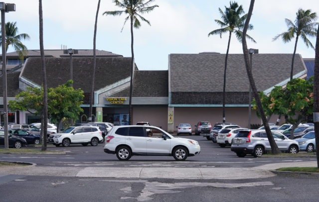 Hawaii Kai Shopping Center showing damaged asphalt and older buildings