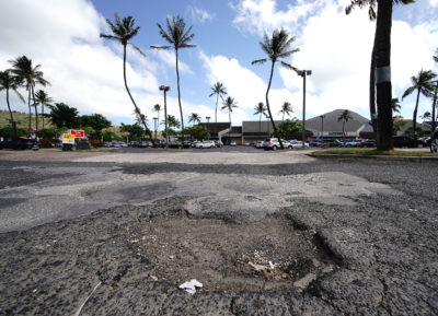 Hawaii Kai Shopping center with large pothole in the parking lot near McDonalds drive thru entrance.
