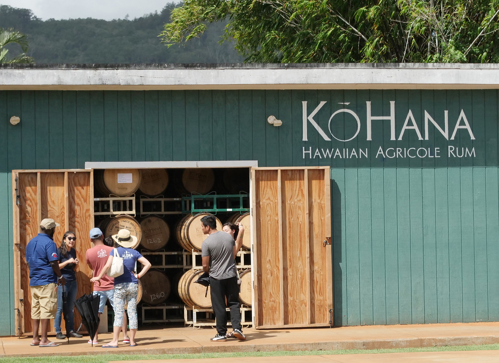 <p>A Ko Hana staff member gives visitors a peak into the barrel room where rum is aged in a variety of wooden barrels. Visitors can take 30-minute tours to learn about the various aspects of rum production.</p>