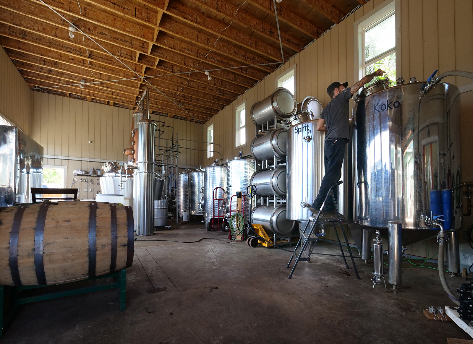 <p>Rum distiller Tyler Johnson checks tanks filled with cane juice. The fermentation process takes about a week and is an important first step before the cane wine can be distilled into rum.</p>