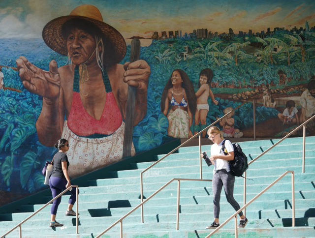 UH Manoa Campus center mural with students walking up and down stairs.