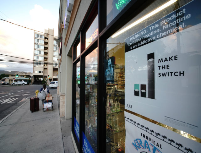 Vape Hawaii Juul advertisement in window 'Make the Switch' with warning, 'This item contains nicotine. Nicotine is a addictive chemical'.