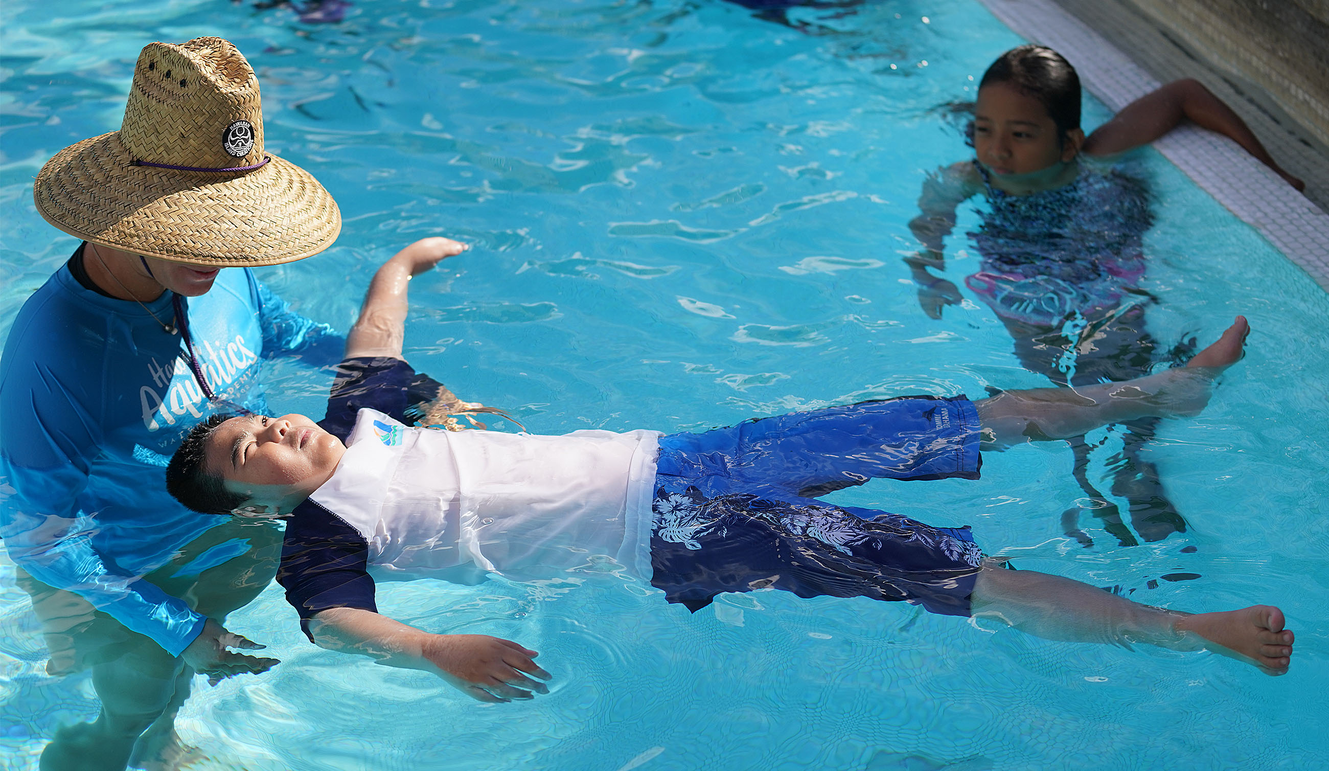 Palama Settlement pool swimming class as student learn how to float on their backs during class.