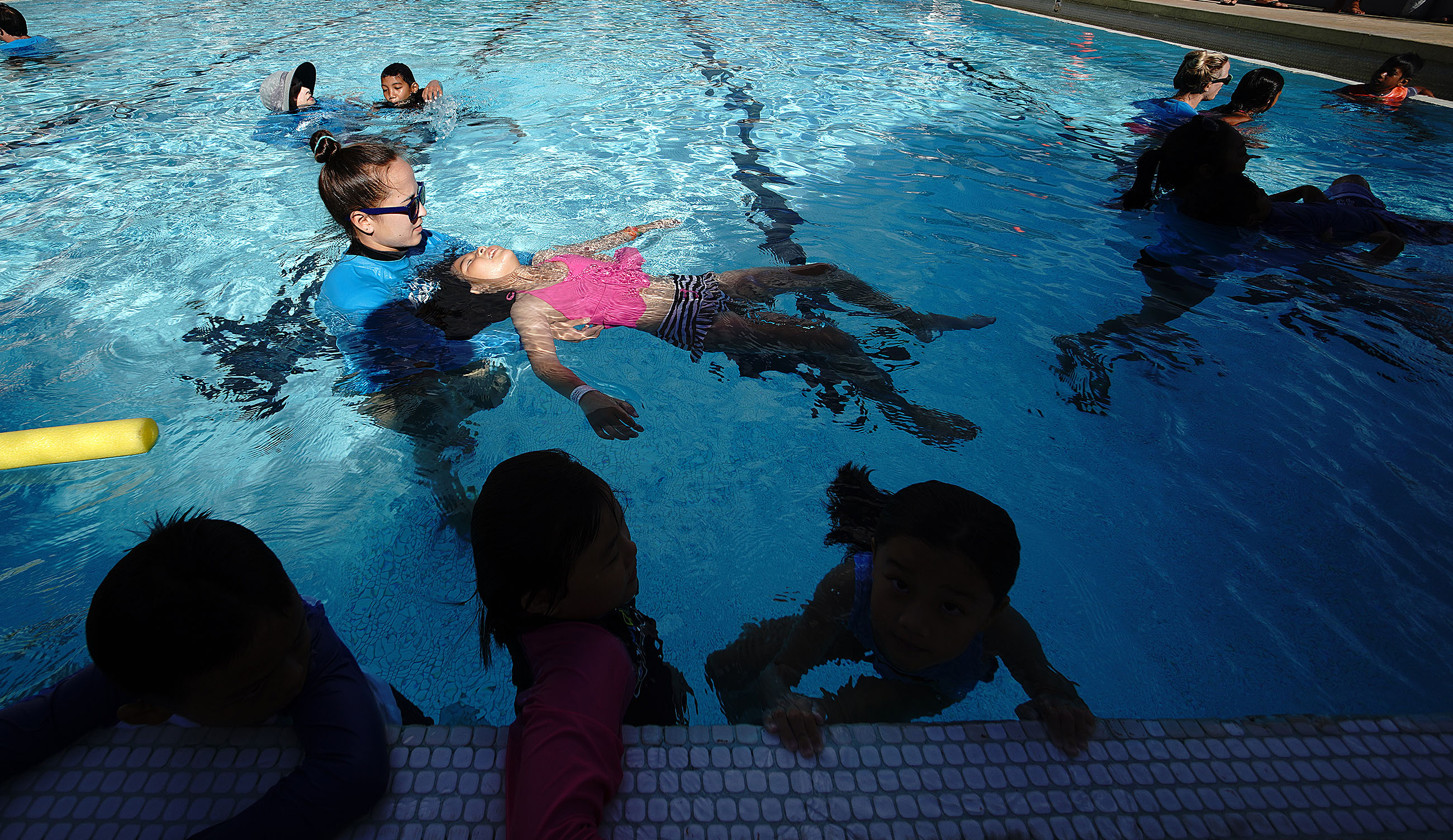 Palama Settlement pool swimming class instructor Tahni Kakazu assists student with back floating during class.
