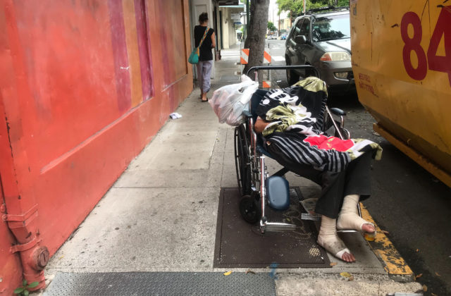 Homeless person covered on Pauahi Street next to the Hawaii Theater.