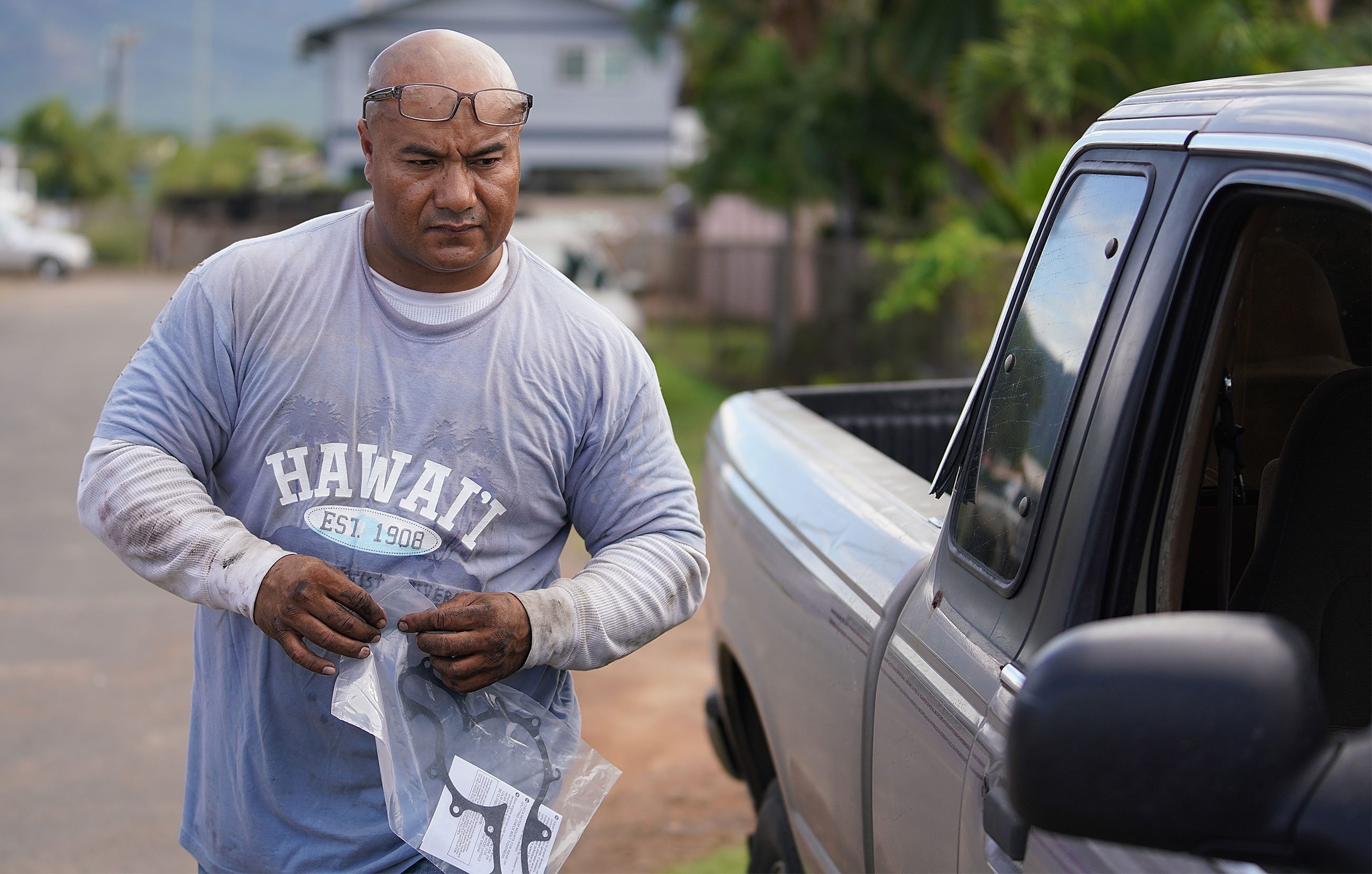Sefo Fataai fixing truck out in Maili Waianae. Sefo holds water pump parts for a truck he is fixing outside along the road.