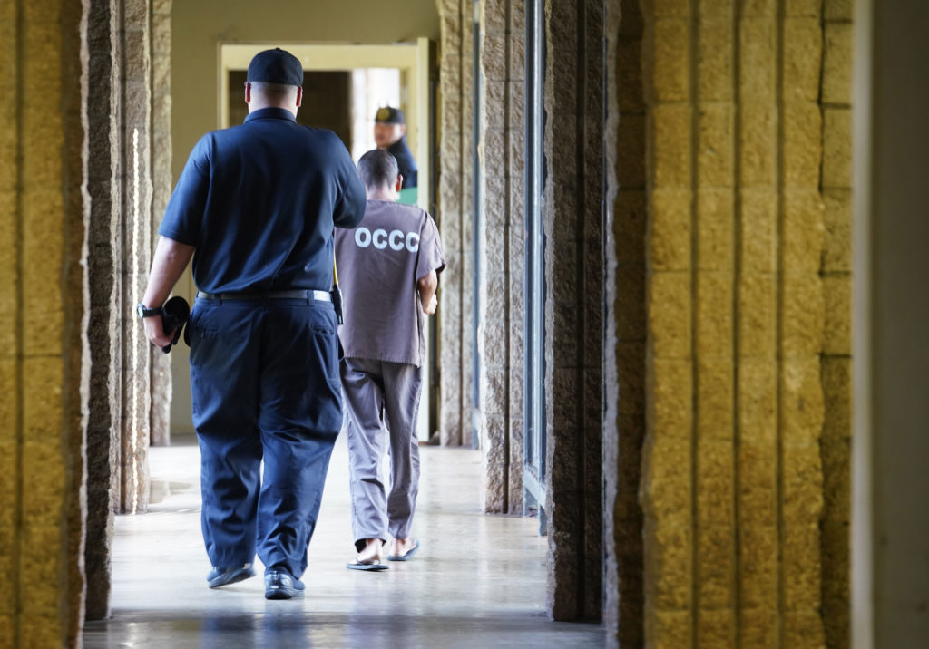 Oahu Community Correctional Center media tour 2019 inmate walks down hall between modules.