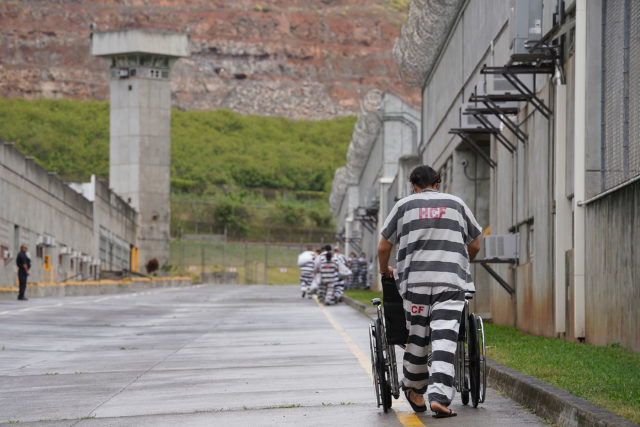 Halawa Correctional Facility inmate pushes empty wheelchair back to module.