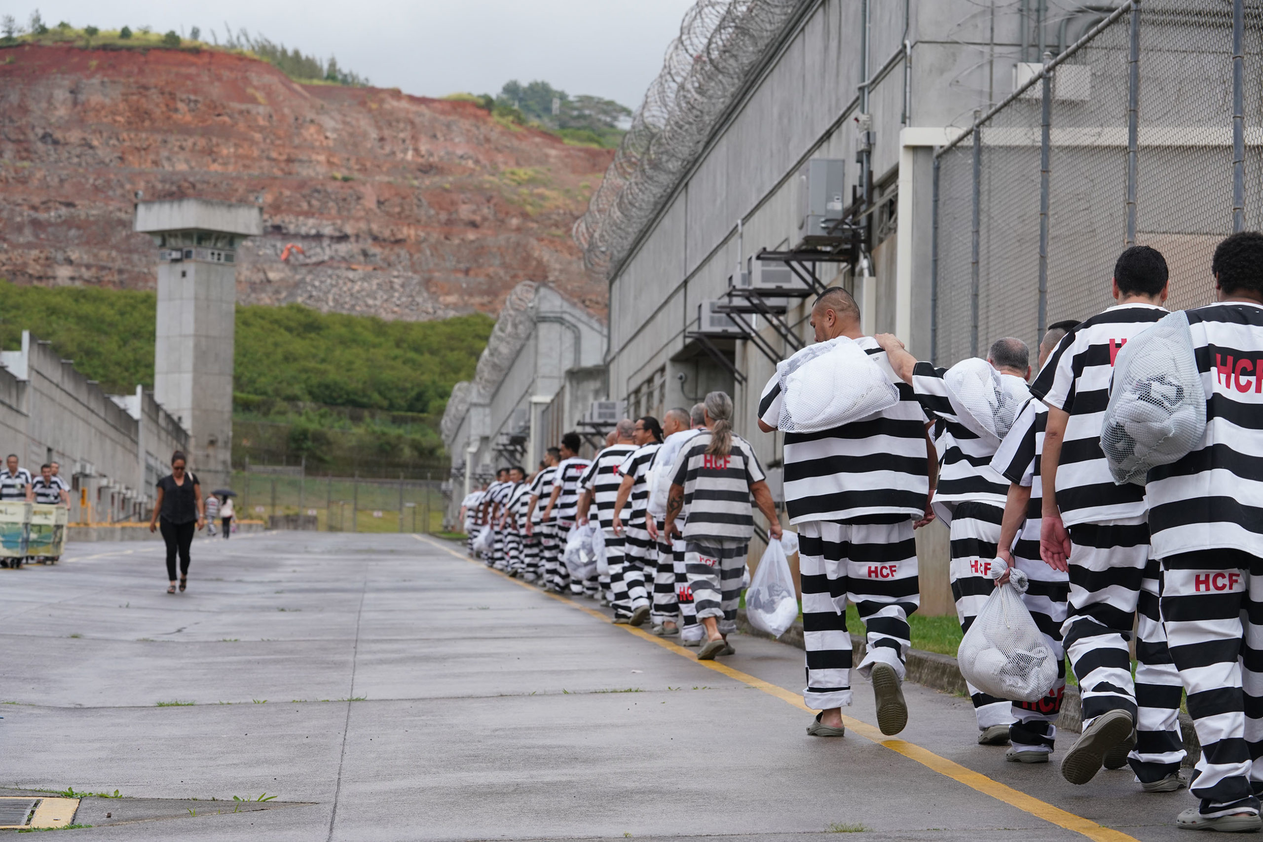 <p>At Halawa Correctional Facility, different color suits indicate different security levels of the inmates. Black stripes are general population, while green are work line inmates, and red are closed security inmates, one level down from maximum security. Maximum security inmates wear orange suits.</p>