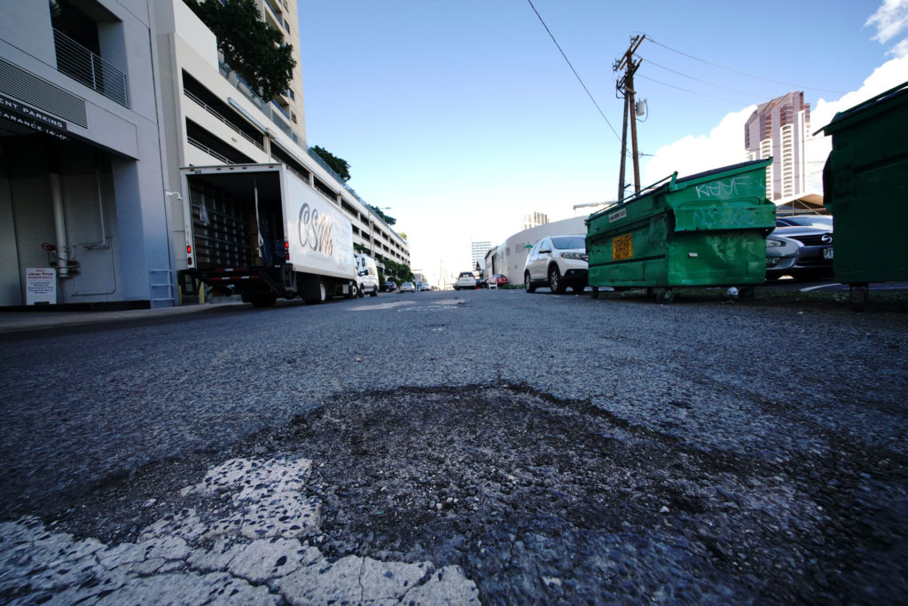 Ilaniwai Street in Kakaako with potholes in foreground.