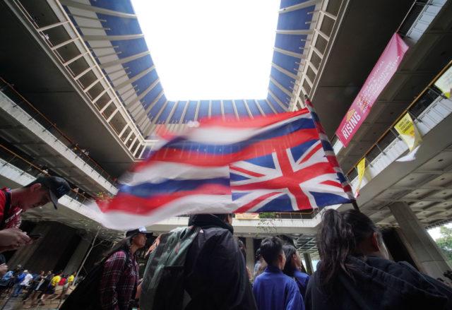 Opening Day of 2020 Legislature flag 9 year old Kawai Kupahu from Kailua holds an upside down flag in the Capitol Rotunda.