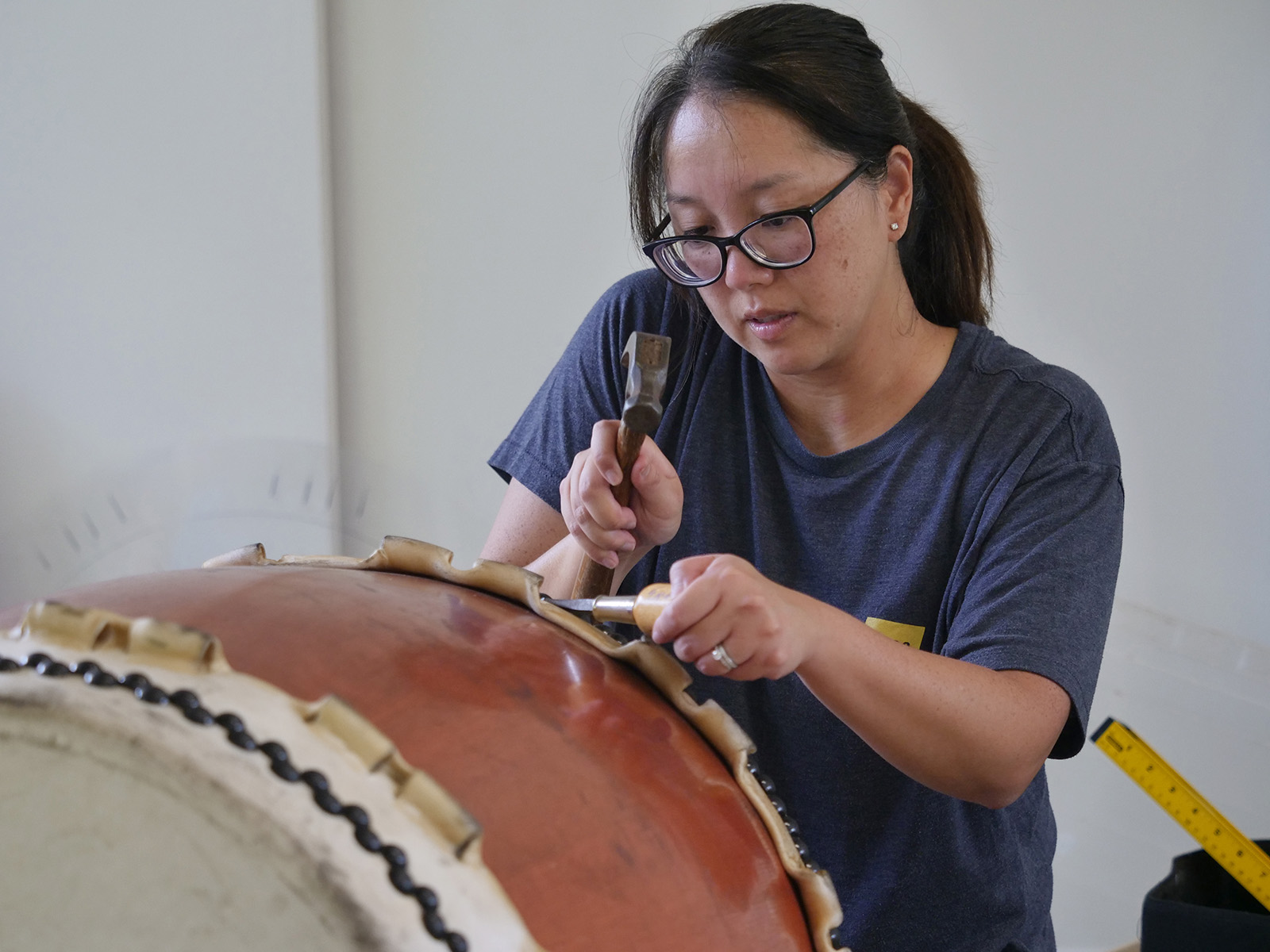 <p>Karyn Doi begins the long process of reskinning a taiko drum by carefully removing the tacks, which hold the skins in place, with a hammer and chisel in Kaneohe.</p>