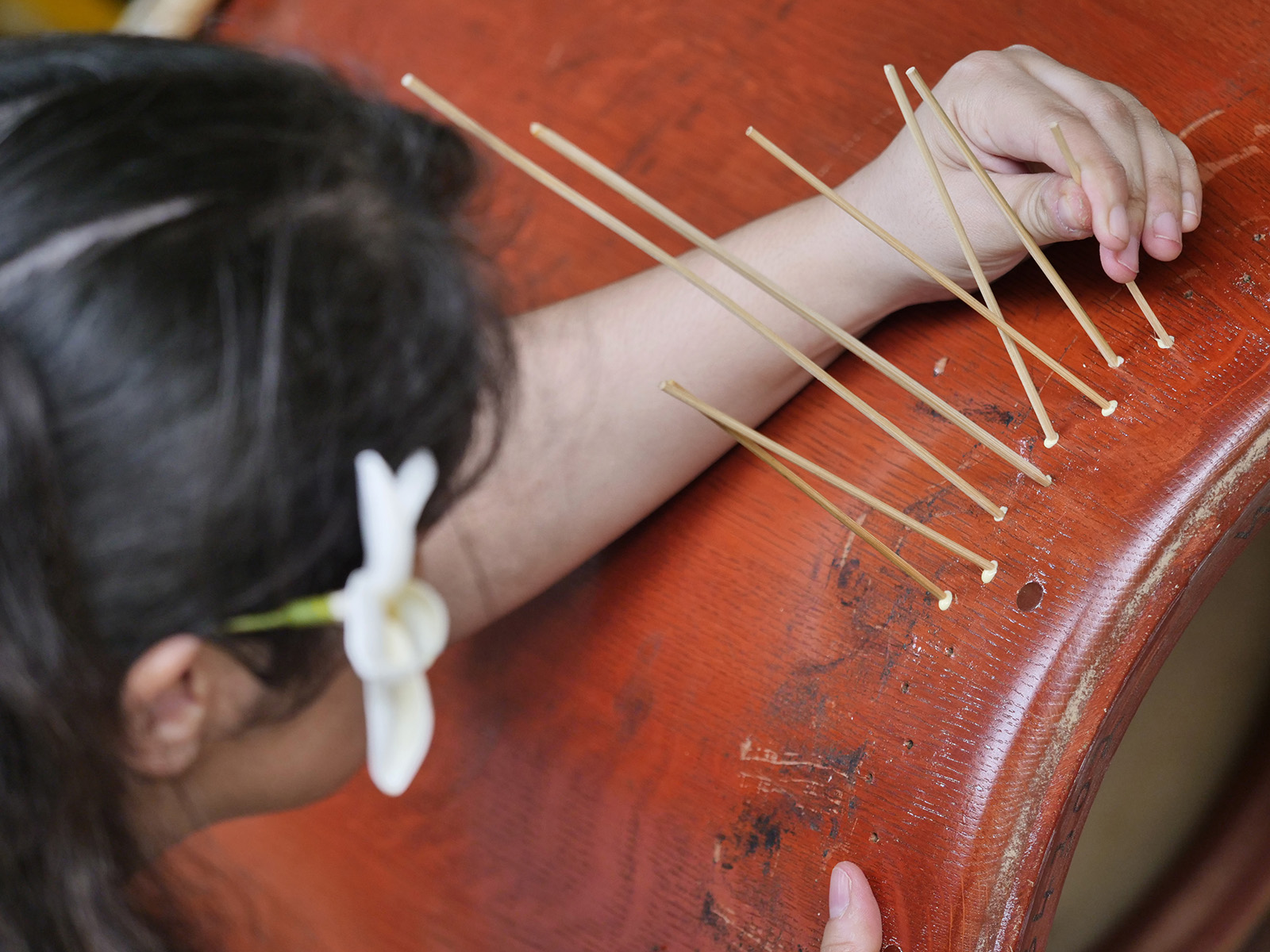 <p>Lani Villanueva glues thin bamboo sticks into holes left by the tacks that secure the drum skins in place. New holes will be drilled to secure the fresh skin once it has been stretched and shaped onto the drum barrel.</p>