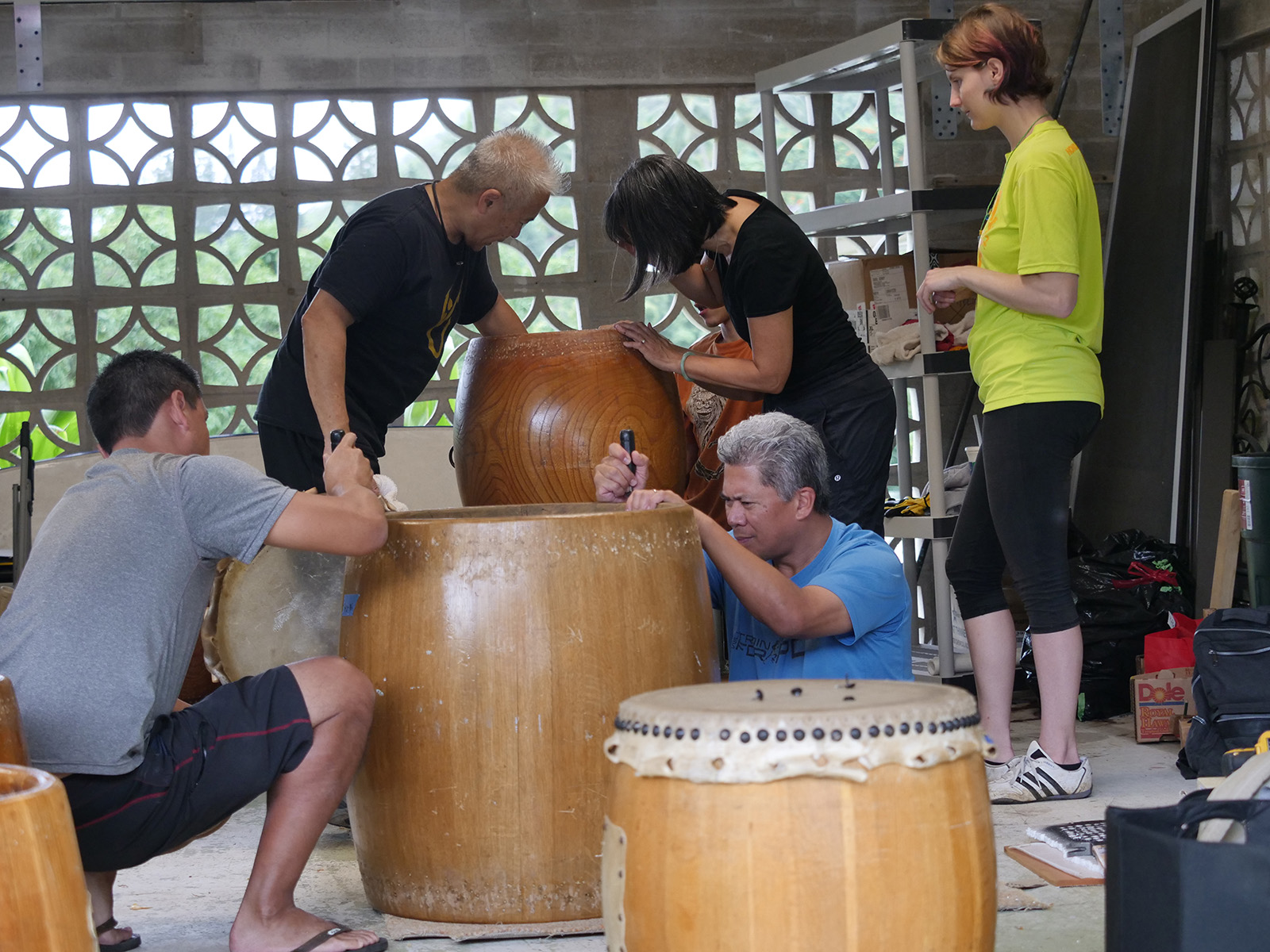 <p>Eric Nouchi, left, and Ray Hose, right, shave and sand recently plugged holes in an odaiko drum so it can be reskinned while Kenny Endo, center left, Tanya Downer, center right, and Elizabeth Mager, far right, inspect a byou-uchi daiko (taiko drum carved from a single piece of wood) for repairs.</p>
