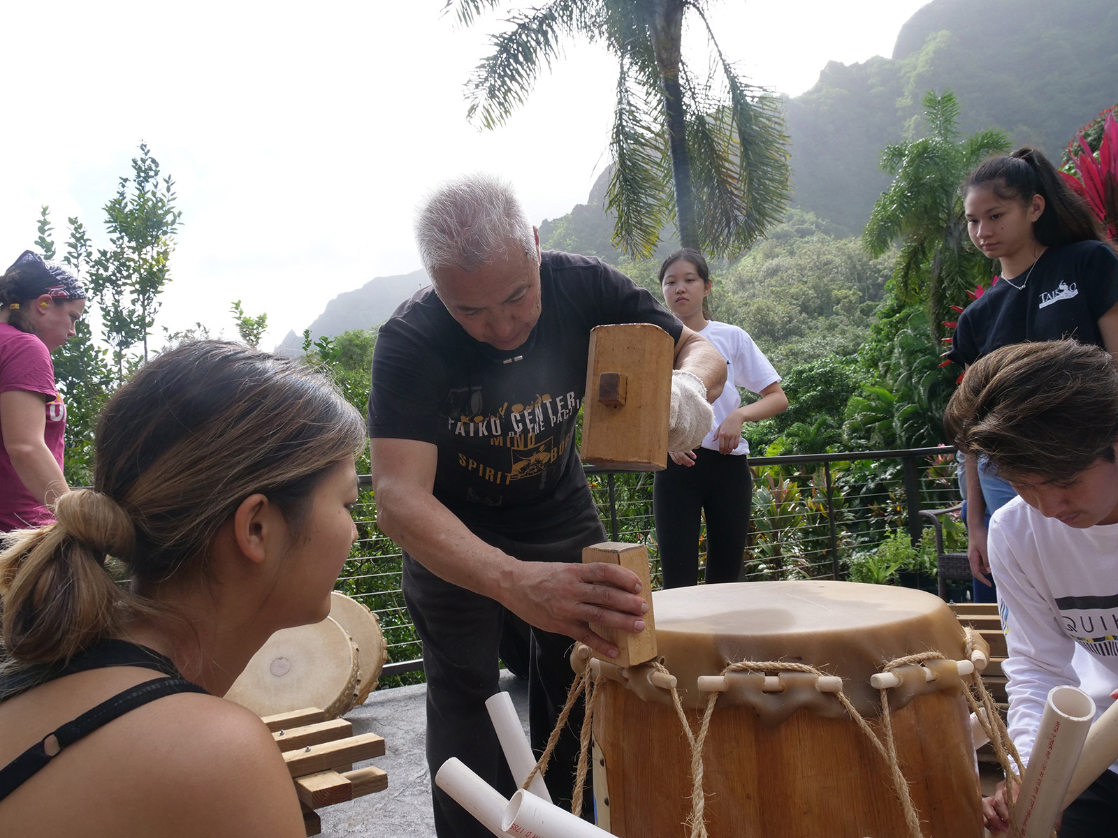 <p>Kenny Endo, center, shows onlookers how to pound down the edges of a cowhide to make sure all sides are even as students, from left, Josie Hung, Elle, Nicole and Curren watch and help to stretch the skin across the top of a taiko drum.</p>