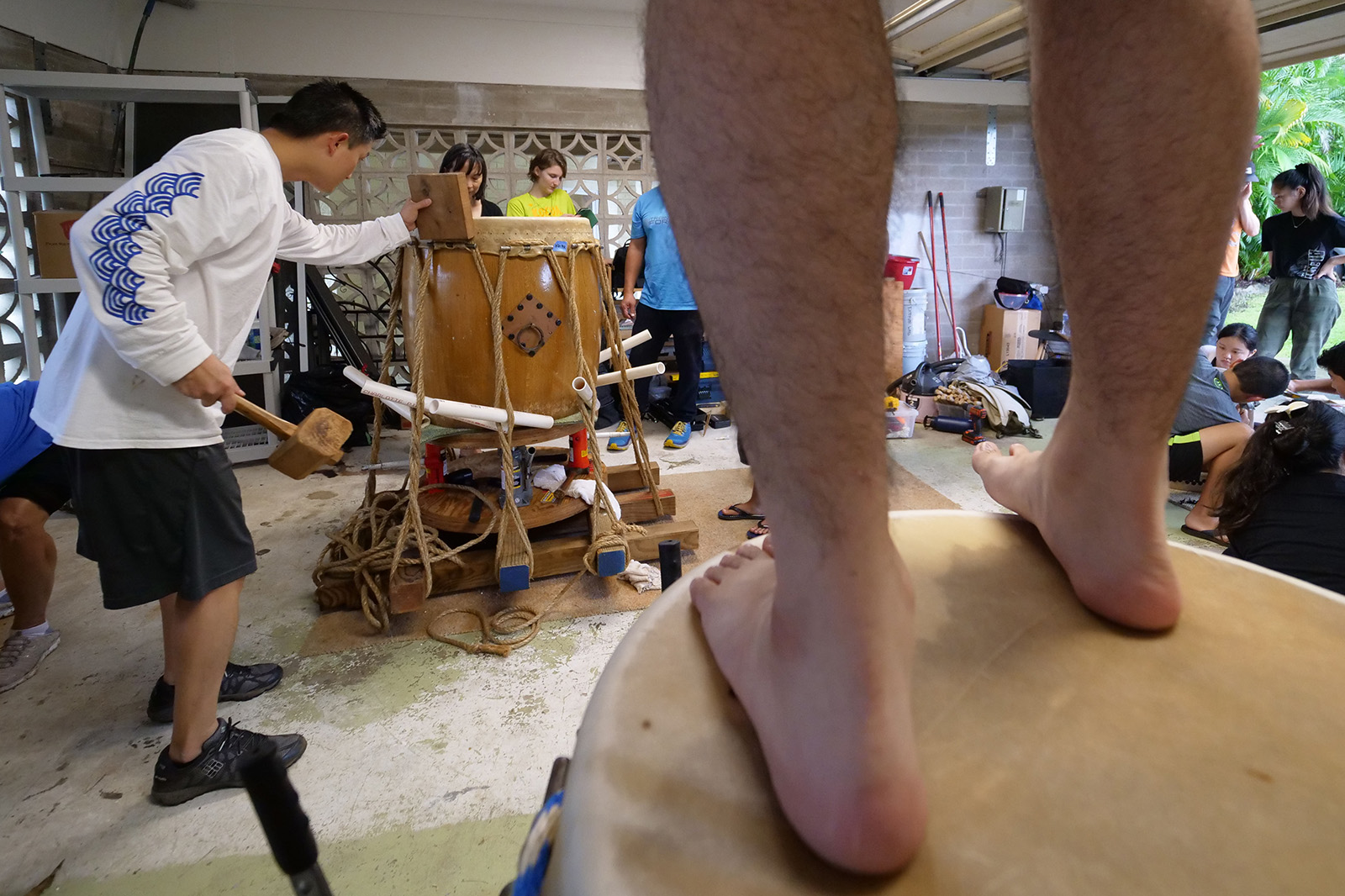 <p>A taiko community member walks atop a drum to massage and loosen the skin further as it is stretched into place as Eric Chang works on stretching the skin of another drum by pounding the edges down.</p>