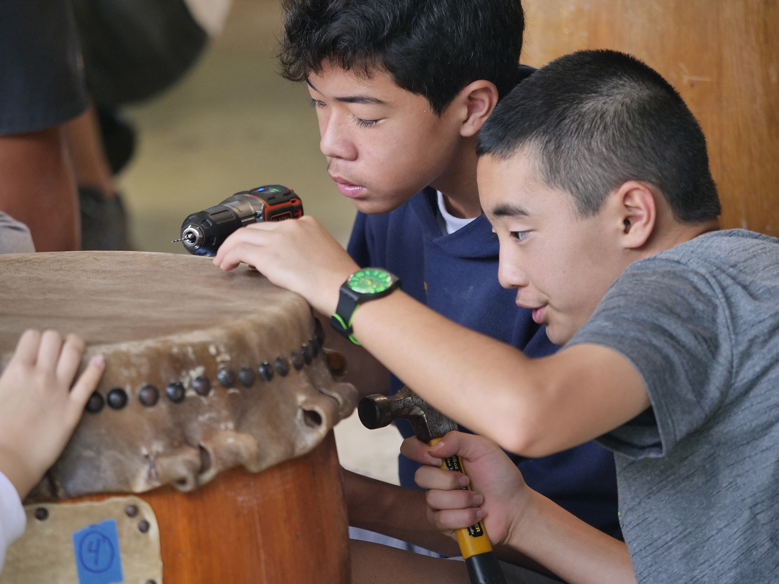 <p>Taiko students Dawson Hose and Blaise Nomitsu hammer small tacks through a thick cowhide once it has dried to secure it onto the wooden drum barrel it has been shaped and stretched to fit. A taiko drum this size uses approximately 200 tacks to hold the skin in place.</p>