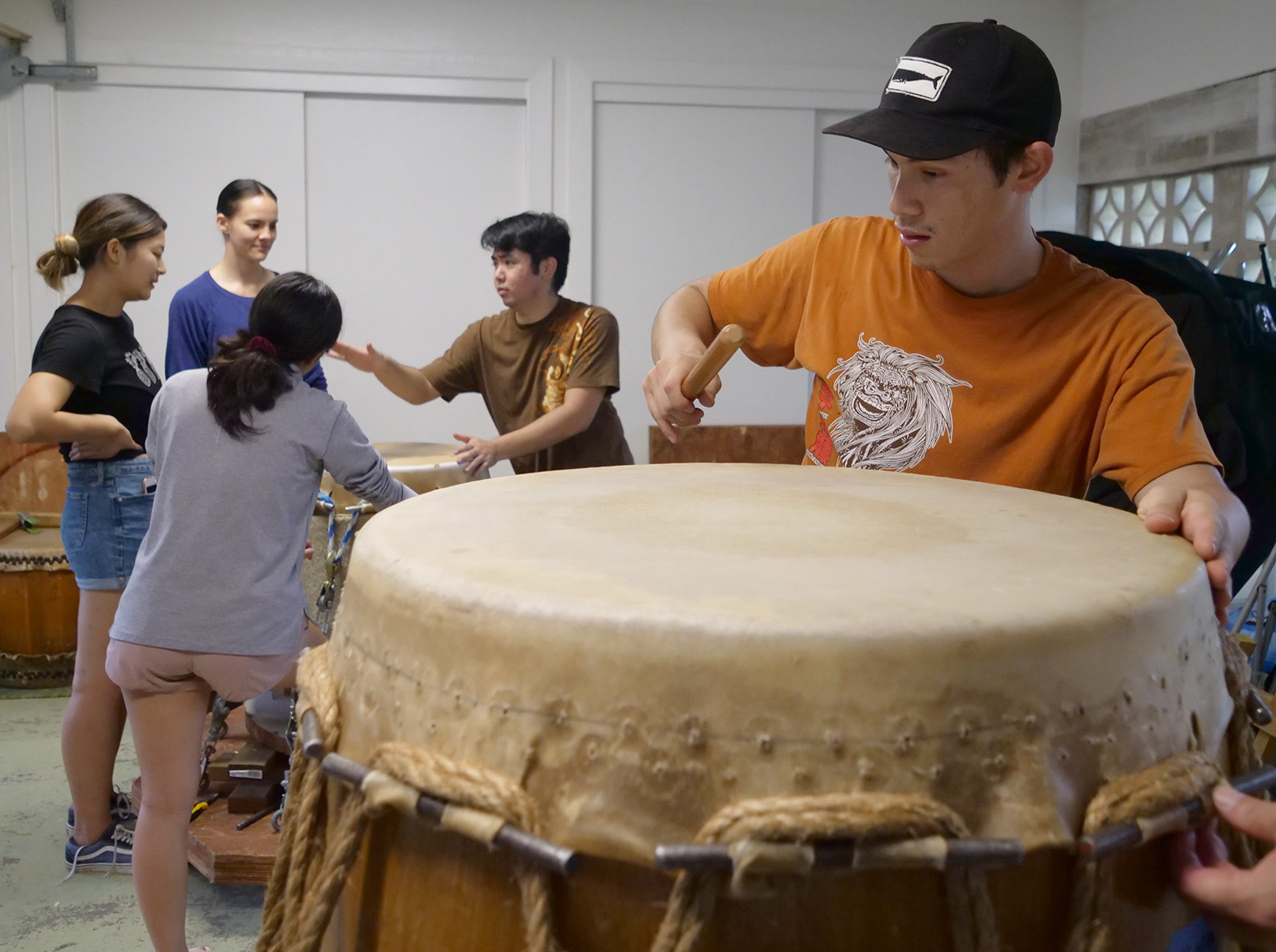<p>Sho'on Shibata gently taps a drumskin to check the sound quality as it slowly dries onto a wooden drum barrel. The skin will continue to be stretched until the desired pitch is reached, at which time it will be tacked into place.</p>