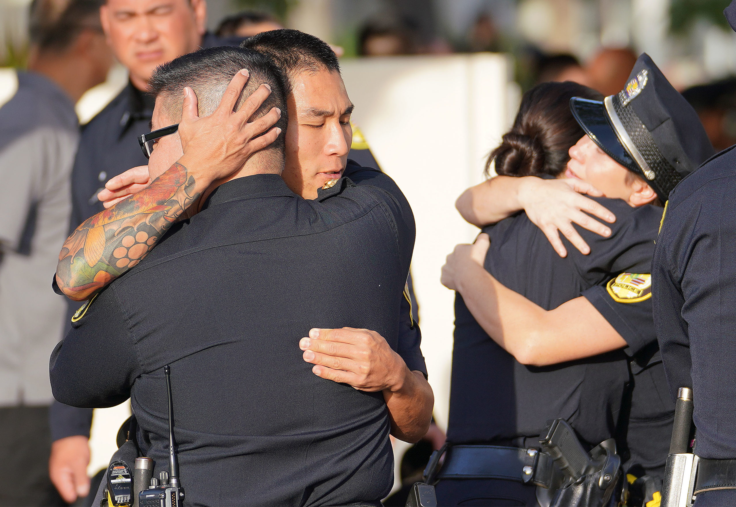 <p>Honolulu police officers consoled each other at Enriquez's memorial service at Diamond Head Memorial Park. Hundreds of  HPD officers attended the service. HPD Deputy Chief John McCarthy has said officers were traumatized by their colleagues' sudden deaths.</p>