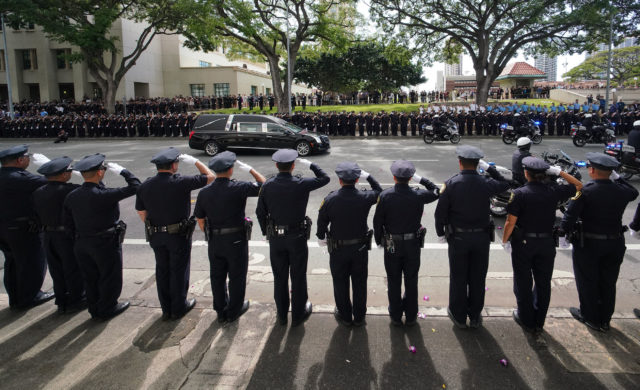 HPD Officers and many other branches of local and national law enforcement salute the procession of vehicles as the body of HPD Officer Tiffany Enriquez heads past the HPD Headquarters.