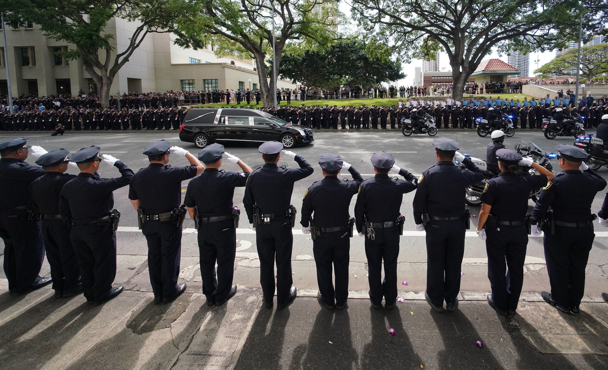 <p>Honolulu police officers saluted the hearse as it drove by the crowd on Beretania Street in front of HPD headquarters. The crowd mostly watched in silence.</p>