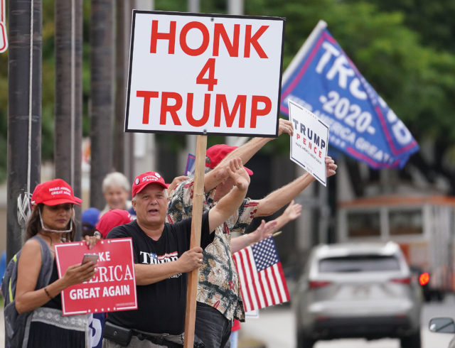President Trump supporters hold signs and wave to motorists near the Capitol on Beretania Street.