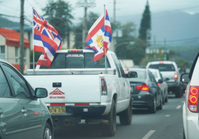 Truck drives down Kamehameha Highway in Kaneohe with Hawaiian flags attached to the bed.