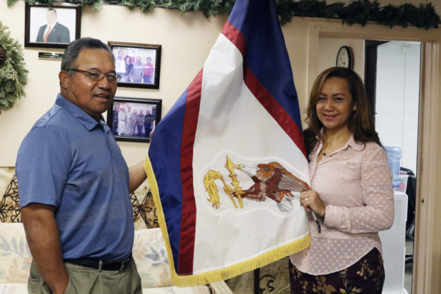 "In this Jan. 10, 2020 photo, Filipo Ilaoa, left, and Bonnelley Pa'uulu pose with the flag of American Samoa at the American Samoa government office in Honolulu. Some American Samoans worry a federal judge's recent ruling in Utah saying those born in the U.S. territory should be recognized as U.S. citizens could threaten ""fa'a Samoa,"" or the Samoan way of life. (AP Photo/Jennifer Sinco Kelleher)"