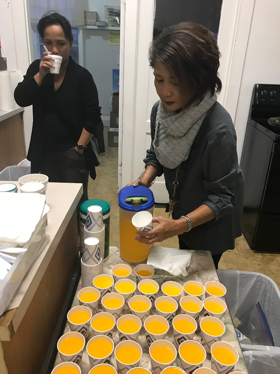 Lisa Shin pours orange juice for kids who attend the Lanai Baptist Church free breakfast every Wednesday.