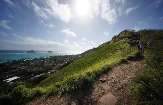visitors hike on the Pillbox Hike overlooking the Mokulua Islands and Lanikai.