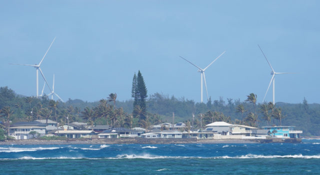 Windmills near Kahuku tower over shoreline homes.
