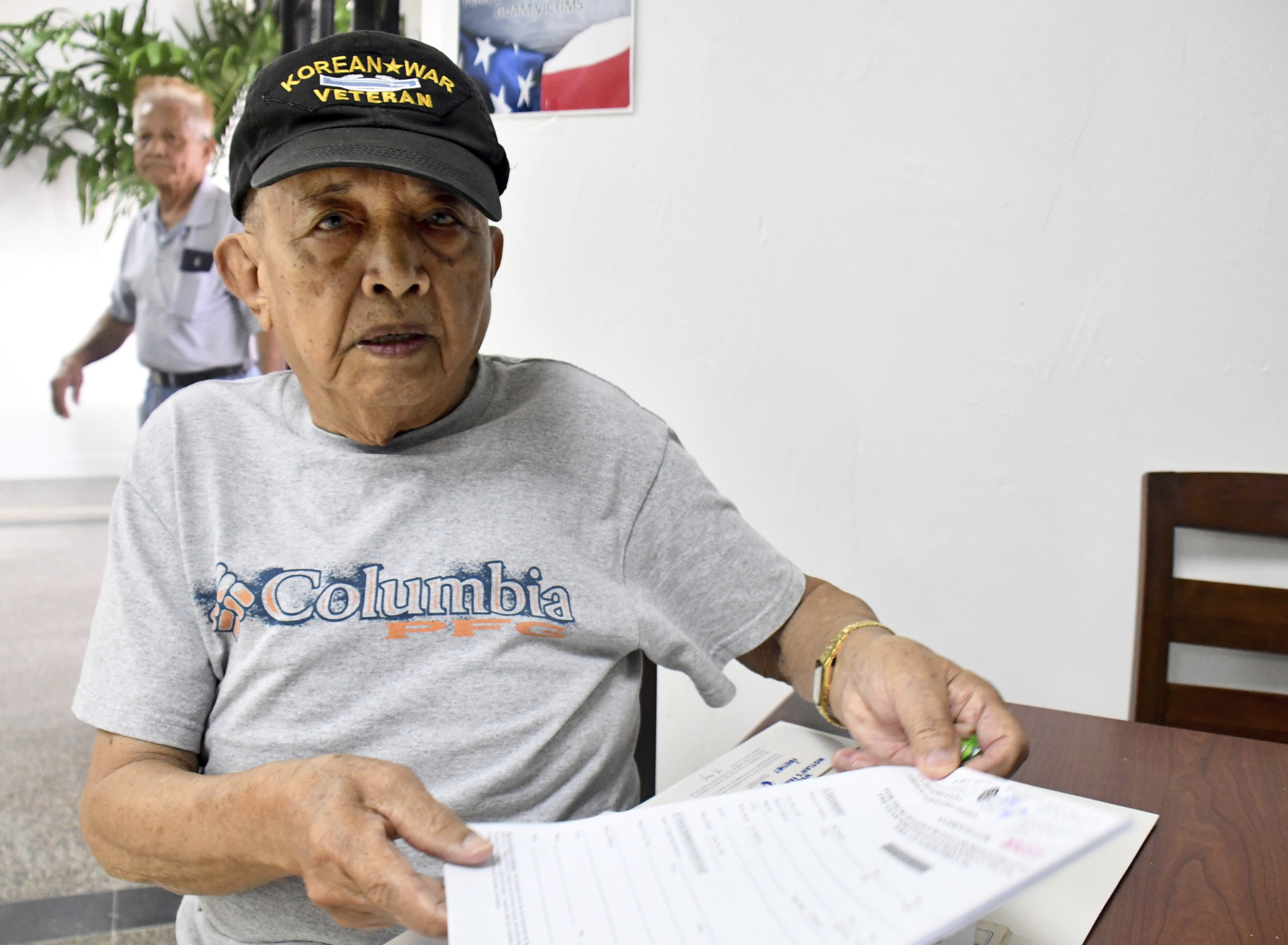 In this Friday, Feb. 7, 2020 photo, Jesus San Nicolas, 86, sits at the Guam war claims office in Tamuning, Guam. The 1941 Japanese invasion of Guam, which happened on the same December day as the attack on Hawaii's Pearl Harbor, set off years of forced labor, internment, torture, rape and beheadings. Now, more than 75 years later, thousands of people on Guam, a U.S. territory, are expecting to get long-awaited compensation for their suffering at the hands of imperial Japan during World War II. (AP Photo/Anita Hofschneider)
