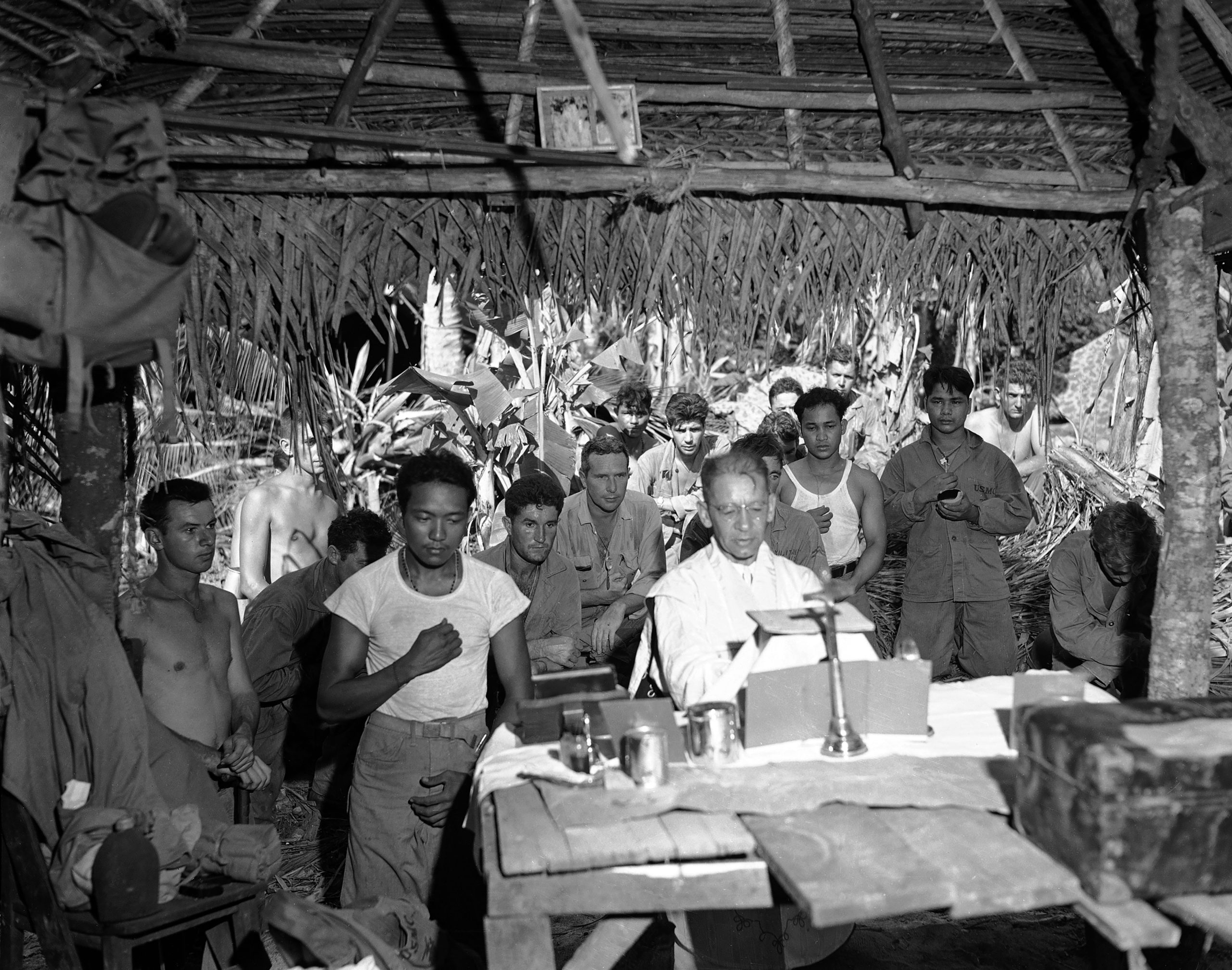 FILE - This Nov. 1, 1944 file photo shows the first religious service on Guam after U.S. landings are attended by soldiers, Nov. 1, 1944. An indigenous Chamorro serves as altar boy in this improvised hut. The 1941 Japanese invasion of Guam, which happened on the same December day as the attack on Hawaii's Pearl Harbor, set off years of forced labor, internment, torture, rape and beheadings. More than 75 years later, thousands of people on Guam, a U.S. territory, are expecting to get long-awaited compensation for their suffering at the hands of imperial Japan during World War II. (AP Photo/Joe Rosenthal, File)