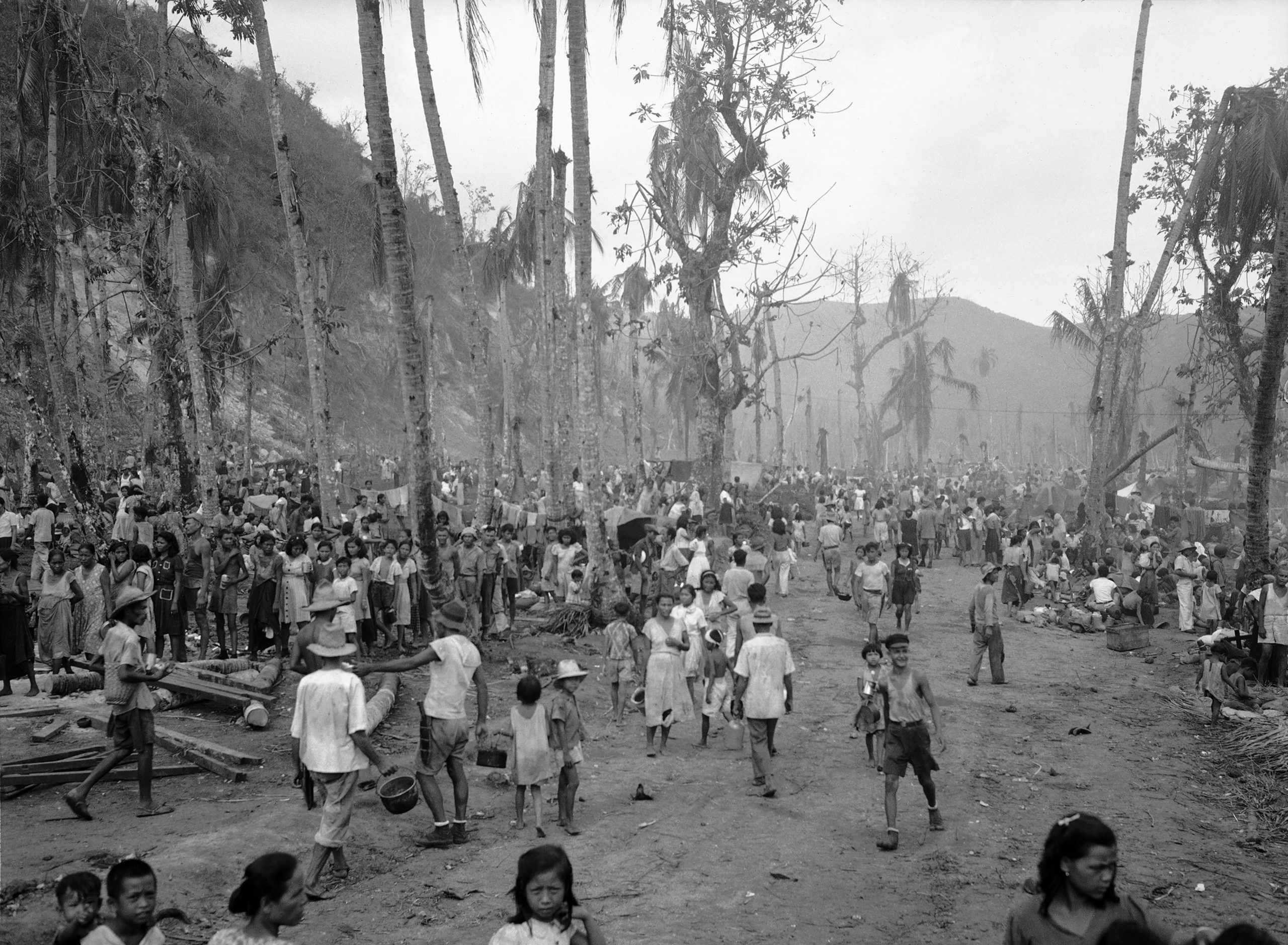 FILE - In this August, 1944 file photo, people of Guam pour out of the hills into the Agana refugee camp. The 1941 Japanese invasion of Guam, which happened on the same December day as the attack on Hawaii's Pearl Harbor, set off years of forced labor, internment, torture, rape and beheadings. More than 75 years later, thousands of people on Guam, a U.S. territory, are expecting to get long-awaited compensation for their suffering at the hands of imperial Japan during World War II. (AP Photo/Joe Rosenthal, File)