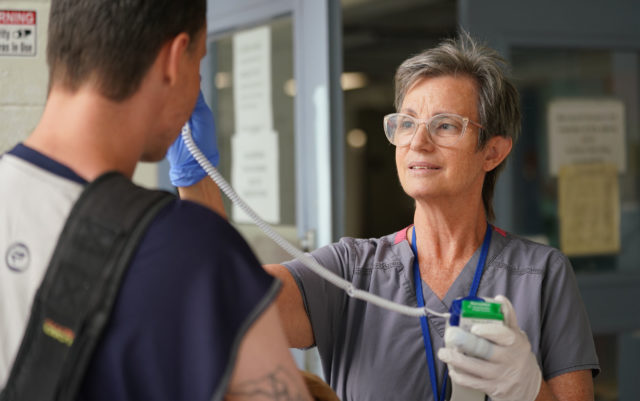 RN Elizabeth Glenn uses thermometer at IHS, she later screened guest with questions about his previous travel itinerary.