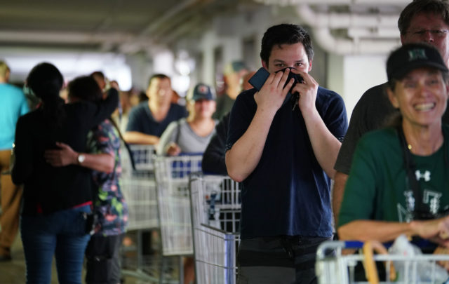 Jay Nordyke holds his shirt over his face wil standing in line with his dad, Thomas Nordyke in the parking lot of Sams Club. The lines snaked from the entrance all the way to the far side of the parking lot.