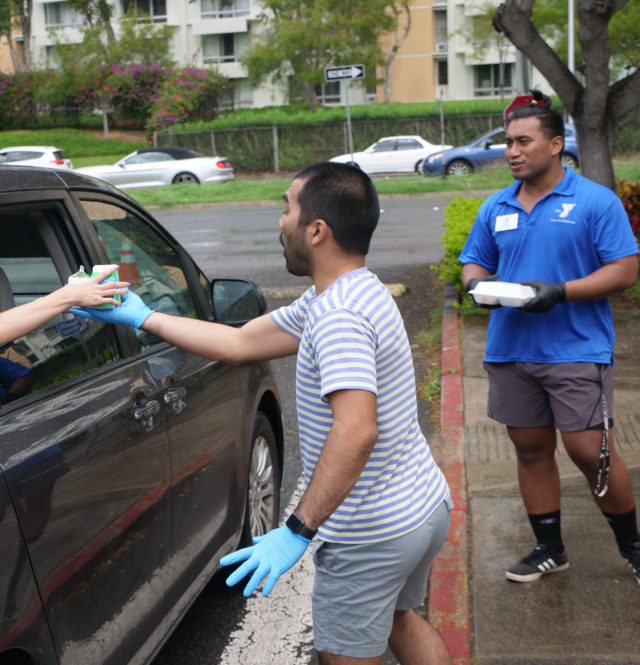 Ikaika Regidor (left) and Edrest (rigt), Nuuanu YMCA volunteers hand out meals to youth in Honolulu, HI, Wednesday, March 25, 2020. The meals are part of an effort to provide food in five neighborhoods highly populated with children and youth who are on the free and reduced lunch program in school. They hope to continue with this emergency meal distribution as long as schools are closed through a collaborative partnership that includes the YMCA of Honolulu Hawaii, Appleseed Aloha Harvest, and The Culinary Institute of the Pacific at Kapiolani Community College. (Ronen Zilberman photo Civil Beat)