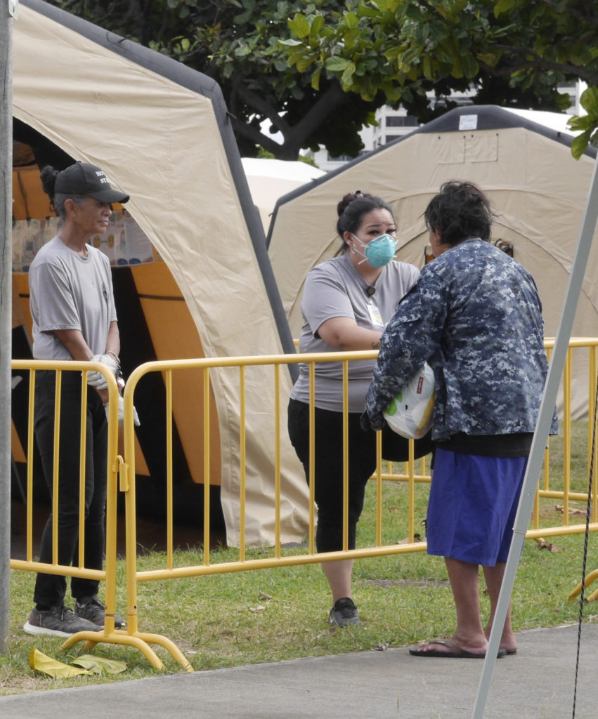 A city & county worker helps by screening a homeless person before allowing him to enter the homeless tent compound set-up in the Old Stadium Park in Honolulu, HI, Saturday, March 28, 2020. (Ronen Zilberman photo Civil Beat)