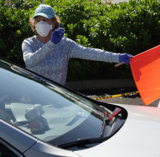 A volunteer nurse practitioner Kari Wilhite helps direct the constant flow of traffic at the drive through COVID-19 test site at the Kaka'ako Waterfront Park in Honolulu, HI, Sunday, March 29, 2020. (Ronen Zilberman photo Civil Beat)