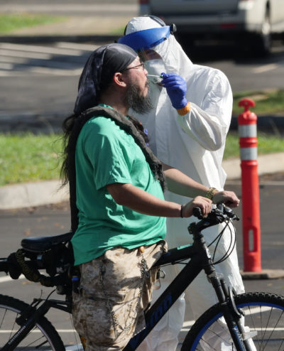 Michael Yoshida has his nose swabbed for the COVID-19 test after riding his bike to the drive through test site set-up at the Kaka'ako Waterfront Park in Honolulu, Sunday, March 29, 2020 in Honolulu, HI. (Ronen Zilberman photo Civil Beat)