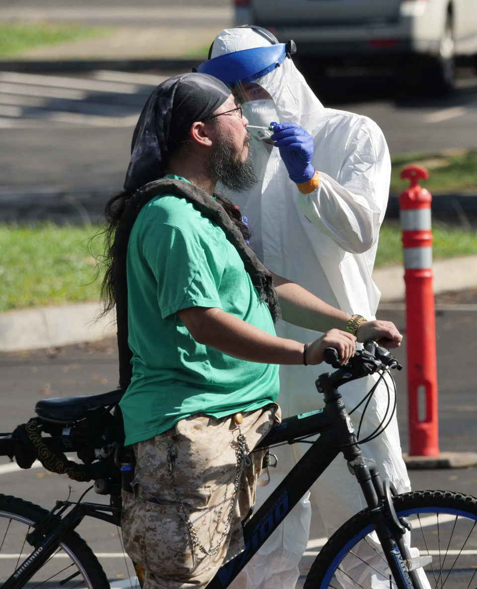 Michael Yoshida has his nose swabbed for COVID-19 after riding his bike to the drive-thru  test site Kakaako Waterfront Park recently.