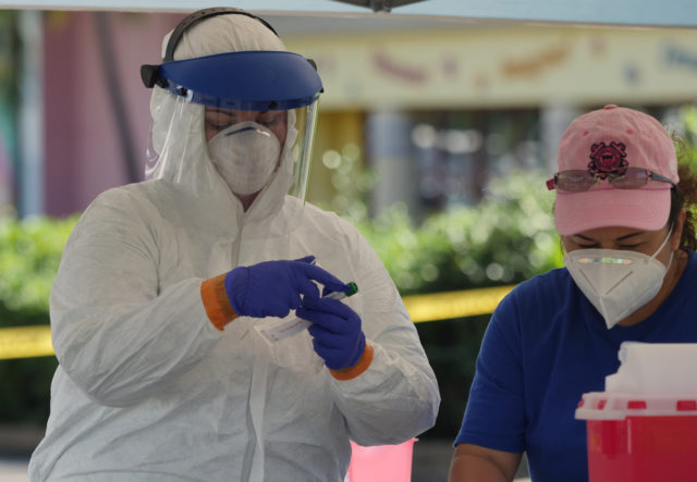 Medical personel seal COVID-19 swab samples into test tubes from the drive through test site at the Kaka'ako Waterfront Park, in Honolulu, HI, Sunday, March 29, 2020. (Ronen Zilberman photo Civil Beat)