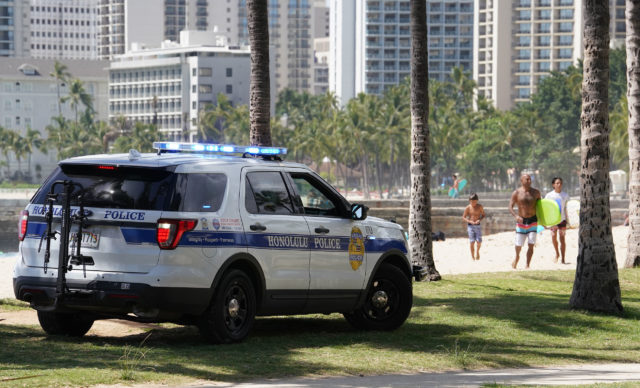 HPD on a loudspeakers tells beachgoers that they cannot be on the beach. Surfing is allowed.