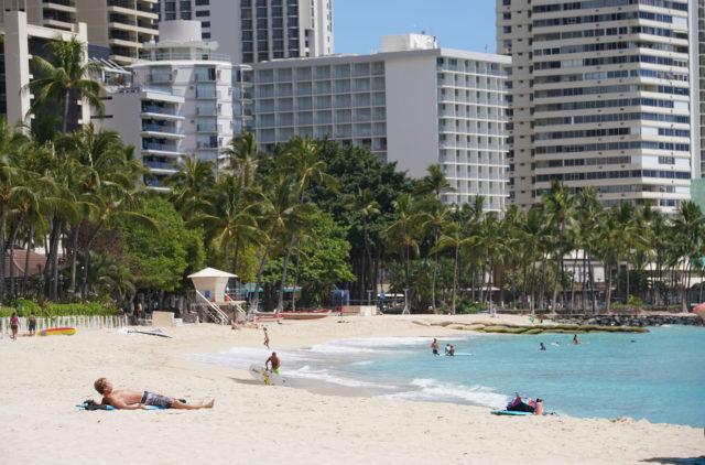 Lone sun bather on Waikiki beach during worldwide Coronavirus pandemic.