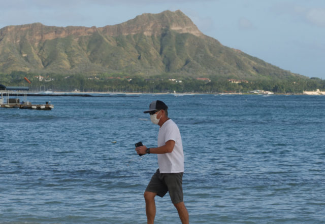 Diamond Head looms in the distance as a masked man walks along the nearly empty beaches in Waikiki, HI on Wednesday, April 1, 2020. (Ronen Zilberman photo Civil Beat)
