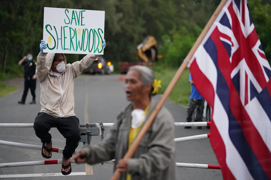 Kalokahi Kauka holds his sign after a large truck with heavy machinery drove into the park area near Sherwood Forest. April 6, 2020.