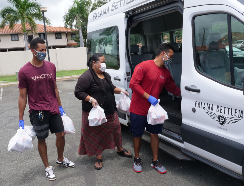 From left, Pi'i Minns, Pauni Nagaseu-Escue, and Miah Ostrowski delives food to homebound Kupuna in Kalihi-Palami on Monday, April 6, 2020.  The food pantry at Palama Settlement has remained open as an essential community service during the COVID-19 quarantines and they are accepting in-kind donations of fresh produce and unexpired canned goods to continue servicing high risk kupuna without transportation. (Ronen Zilberman photo Civil Beat)